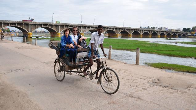 bike rickshaw tourists on river bank jpg